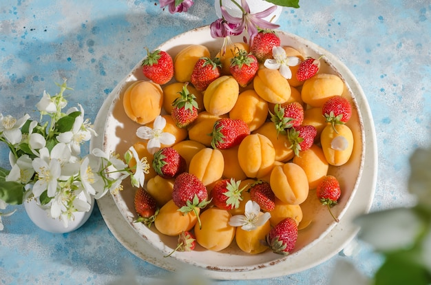 Dojrzałe świeże jagody i owoce - morele, truskawki w talerzu na niebieskim tle