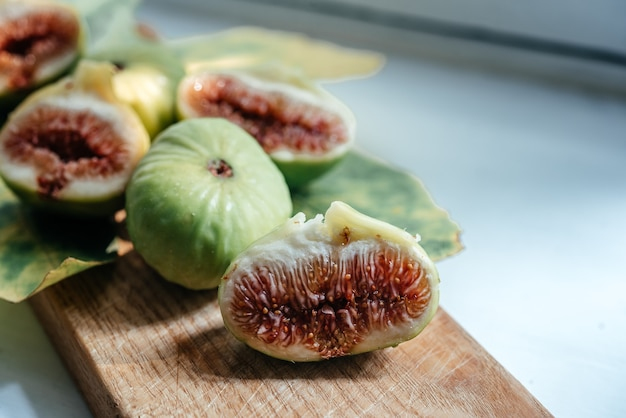 Dojrzałe świeże owoce figowe i liść na białym tle