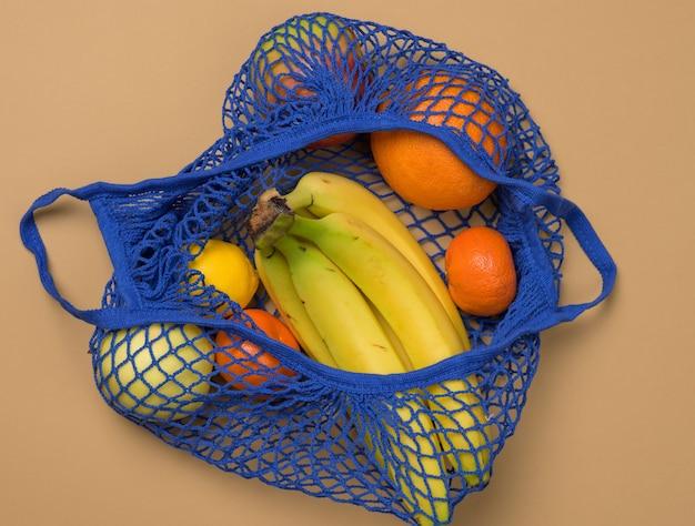 Dojrzałe, świeże owoce w tekstylnej torbie sznurkowej na brązowym tle, widok z góry