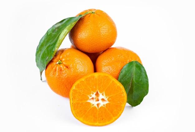 Dojrzałe, świeże, soczyste mandarynki z liśćmi na białym tle