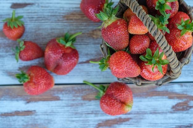 Dojrzałe świeże truskawki ogrodowe w wiklinowym koszu vintage na drewnianym tle