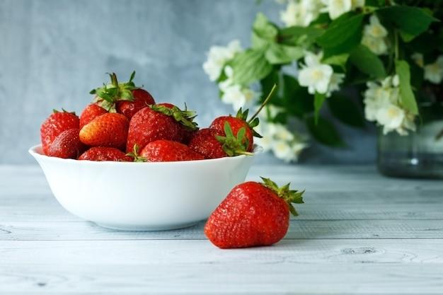 Dojrzałe truskawki na białym talerzu i kwiatach jaśminu