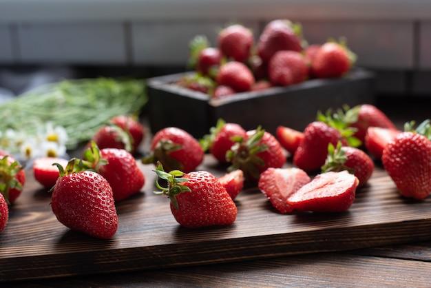 Dojrzałe truskawki na desce do krojenia w kuchni z bukietem stokrotek, koncepcja lato, z bliska.