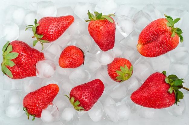 Dojrzałe truskawki na lodzie. przechowywanie jagód. schłodzone owoce.
