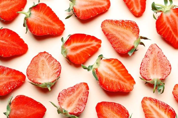 Dojrzałe truskawki soczyste na różowym tle. wzór. twórczy lato kompozycja tło z plastrami truskawek. minimalna koncepcja owoców.