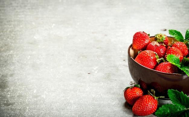 Dojrzałe truskawki w misce. na kamiennym stole.