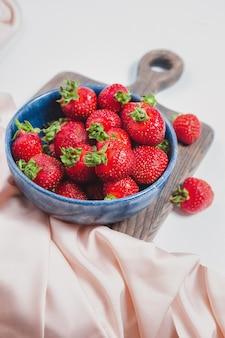 Dojrzałe truskawki w niebieskiej misce na rustykalnej desce, elegancki styl, słodkie jagody na letni deser. napełniona miska lub talerz czerwonymi świeżymi truskawkami. zbiory sezonowe. eleganckie tło truskawkowe