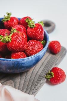 Dojrzałe truskawki w niebieskiej misce na rustykalnej desce, elegancki styl, słodkie jagody na letni deser. napełniona miska lub talerz czerwonymi świeżymi truskawkami. zbiory sezonowe