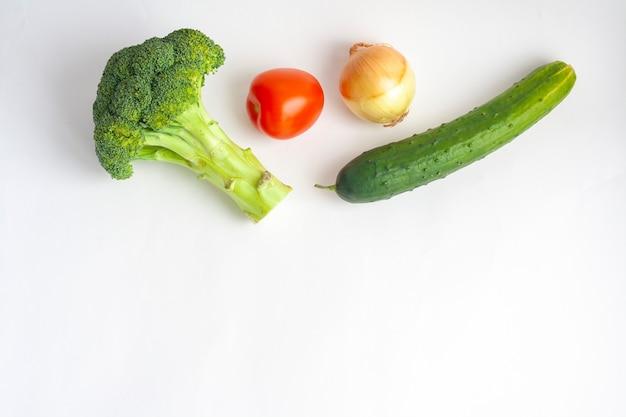 Dojrzałe warzywa brokuły, pomidor, ogórek i cebula na białym tle