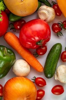 Dojrzałe warzywa płaskie składają się z warzyw sałatkowych, takich jak marchew i pomidory koktajlowe na białej podłodze
