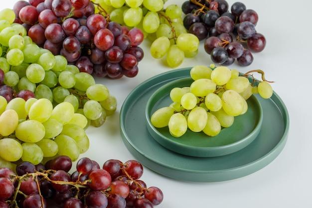 Dojrzałe winogrona w spodeczku z płytą wysoki kąt widzenia na białym