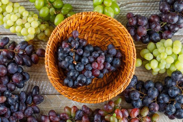 Dojrzałe winogrona w wiklinowym koszu na drewnianym tle. leżał płasko.