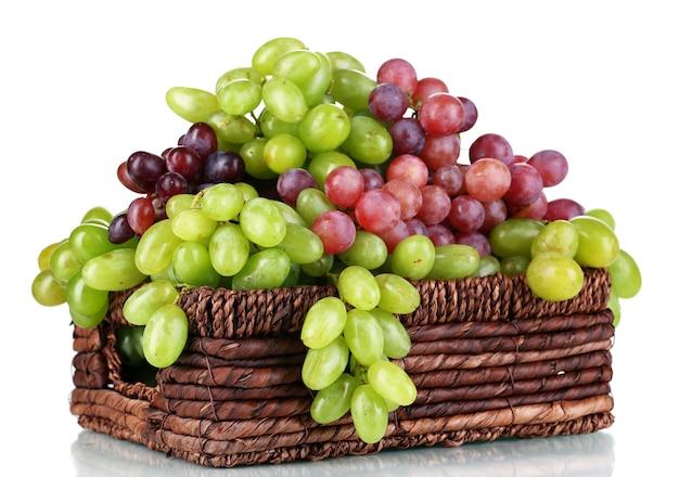 Dojrzałe winogrona zielone i fioletowe w koszyku na białym tle