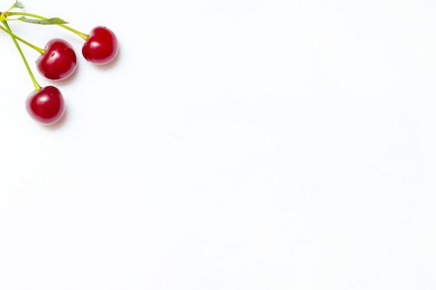 Dojrzałe wiśnie na białym liściu w lewym górnym rogu.