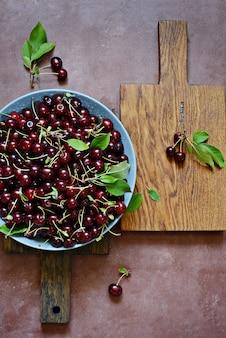 Dojrzałe wiśnie w szarej misce na desce. smaczna letnia jagoda.