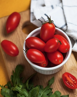 Dojrzałe, wydłużone pomidorki koktajlowe z zielonymi liśćmi w białym talerzu na drewnianym