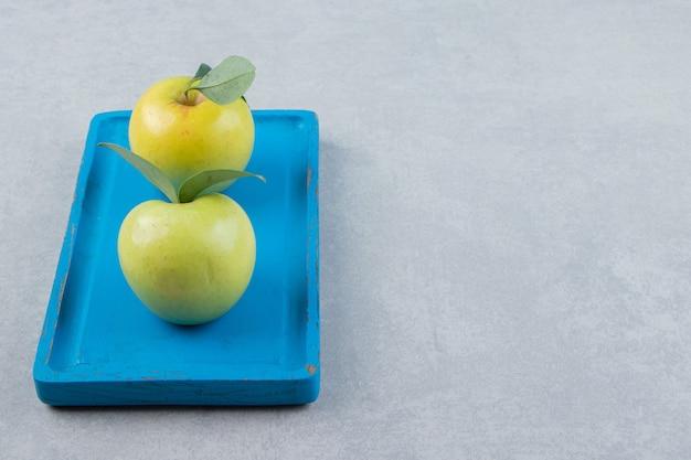 Dojrzałe zielone jabłka na niebieskim talerzu.