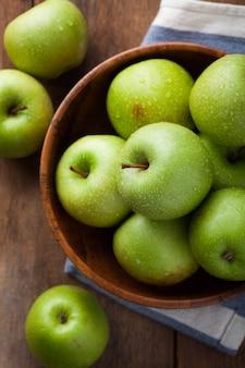 Dojrzałe zielone jabłka w drewnianej misce.