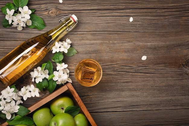 Dojrzałe zielone jabłka w drewnianym pudełku z gałęzi białych kwiatów, szkła i butelki cydru na drewnianym stole. widok z góry z miejscem na tekst.
