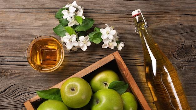 Dojrzałe zielone jabłka w drewnianym pudełku z gałęzi białych kwiatów, szkła i butelki cydru na drewnianym stole. widok z góry.