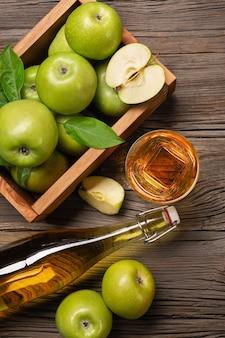 Dojrzałe zielone jabłka w drewnianym pudełku z gałęzi białych kwiatów, szkła i butelki świeżego soku na drewnianym stole. widok z góry.