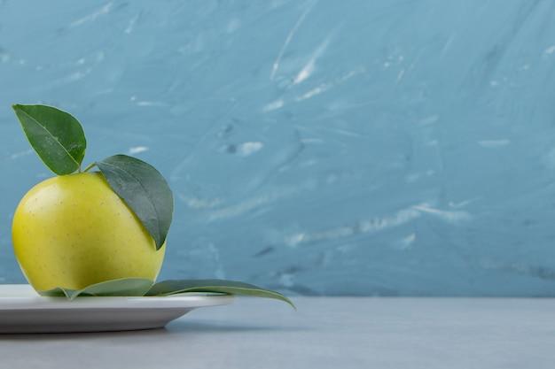 Dojrzałe zielone jabłko na białym talerzu.