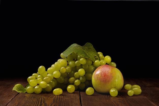 Dojrzałe zielone winogrona i słodkie jabłko na drewnianym stole na ciemnym tle.