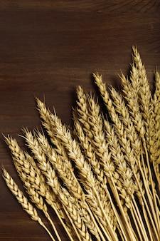 Dojrzałe złote kłosy pszenicy na powierzchni drewnianych