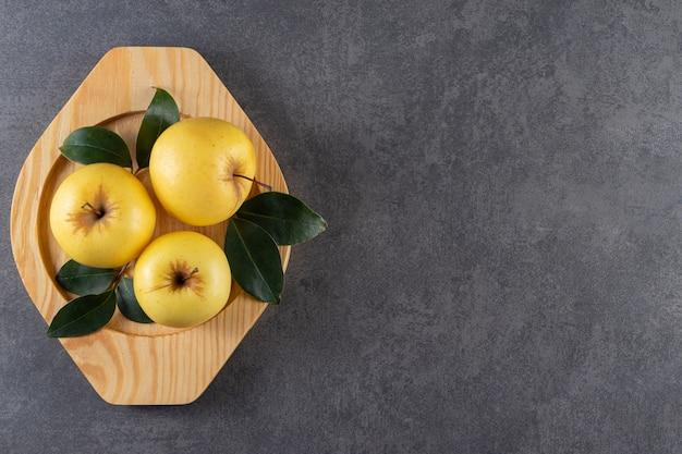 Dojrzałe żółte jabłka z zielonymi liśćmi na drewnianym talerzu.