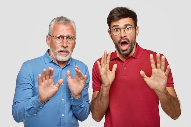 Dojrzali i dorośli mężczyźni mają przerażone miny, widzą coś przerażającego z przodu, gestykulują rękami jako próba obrony, nosi okrągłe okulary, patrzą z wyskoczonymi oczami, odizolowani od białej ściany