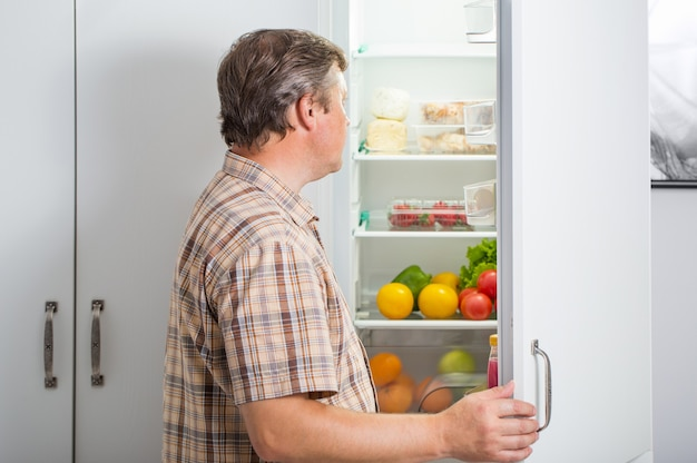 Dojrzali mężczyźni przy lodówce z jedzeniem