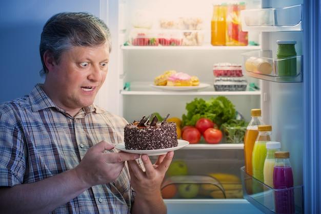 Dojrzali mężczyźni w lodówce z jedzeniem
