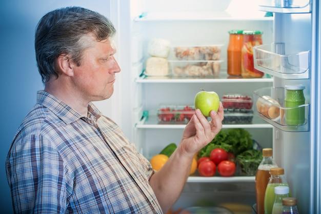 Dojrzali mężczyźni w lodówce z zielonym jabłkiem