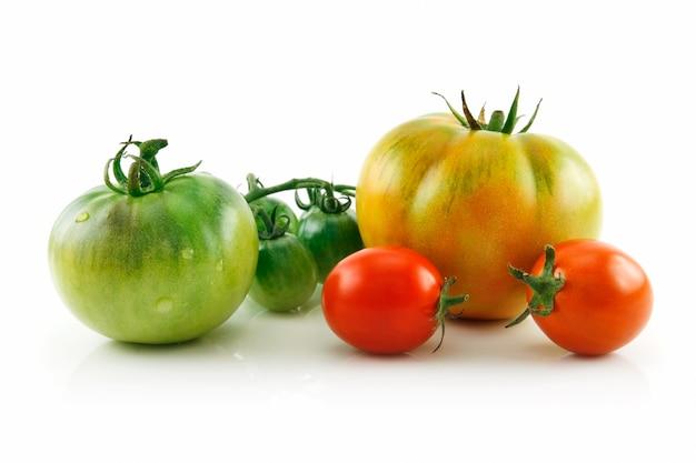 Dojrzali mokrzy czerwoni i żółci pomidory odizolowywający na białym tle