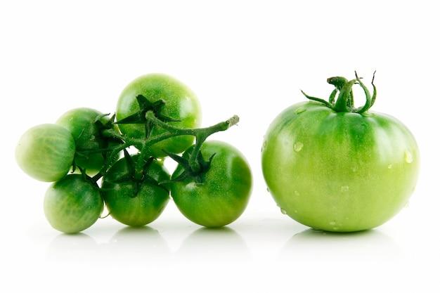 Dojrzali mokrzy zieleni pomidory odizolowywający na białym tle