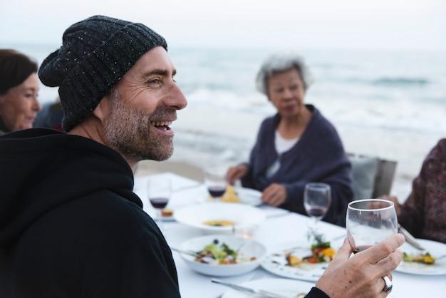 Dojrzali przyjaciele pije wino przy plażą