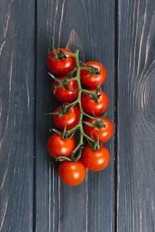 Dojrzali świezi czereśniowi pomidory na gałąź przeciw czarnej drewnianej desce