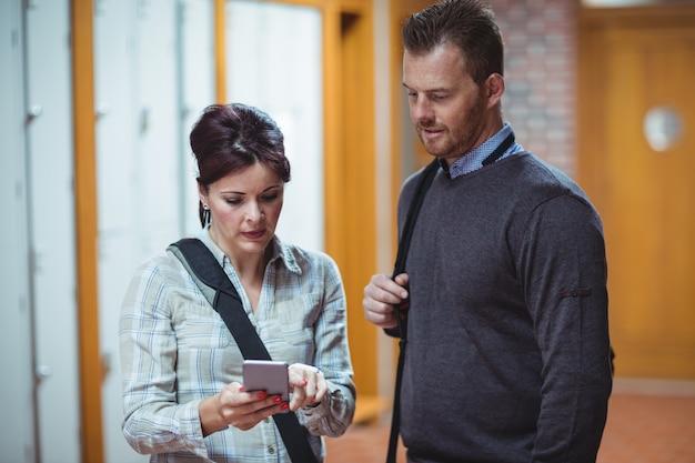 Dojrzali ucznie dyskutuje nad telefonem komórkowym