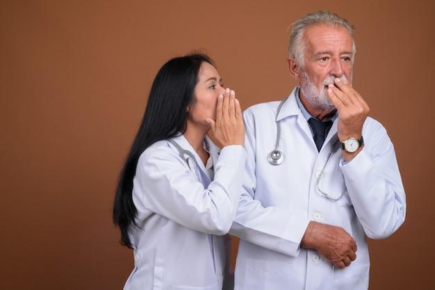 Dojrzali wieloetniczni para lekarze na brązie