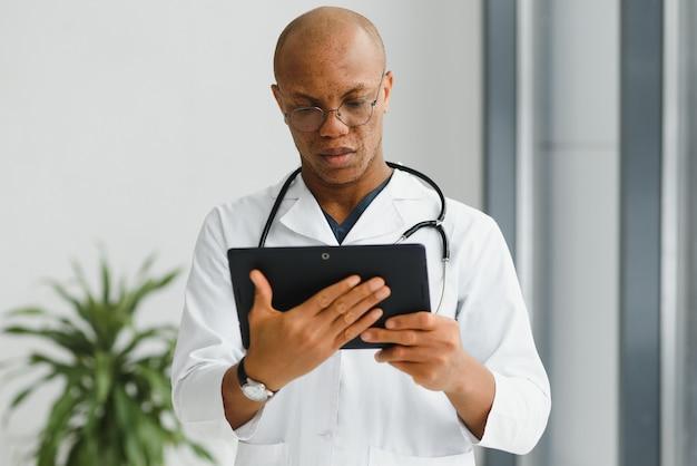 Dojrzały afrykański lekarz za pomocą cyfrowego tabletu na korytarzu