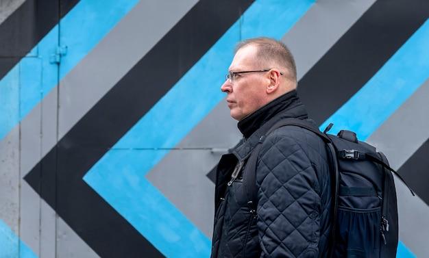 Dojrzały ambitny człowiek idzie i czeka na czarne i szare strzałki na ścianie budynku. koncepcja strategii i kierunku.
