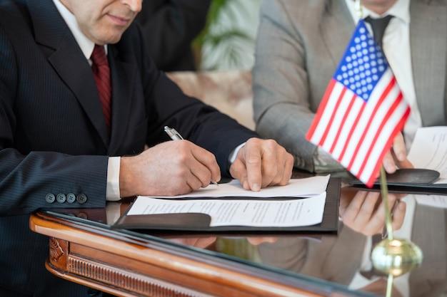 Dojrzały amerykański delegat w stroju formalnym podpisuje umowę o partnerstwie biznesowym z zagranicznym partnerem siedząc przy stole w sali konferencyjnej