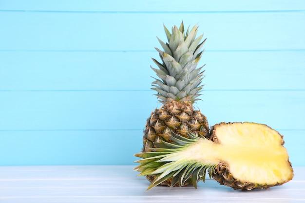 Dojrzały ananas i połówka ananasa na błękitnym drewnianym tle