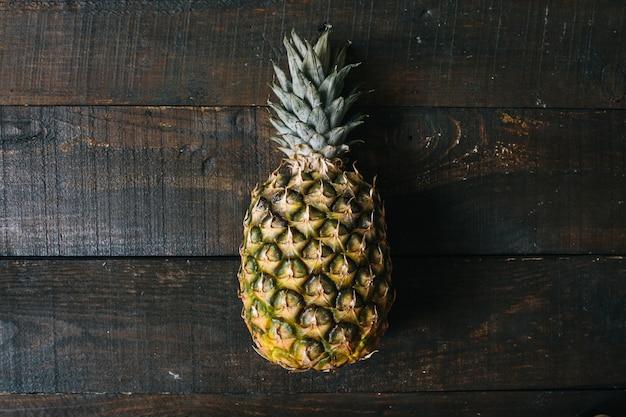 Dojrzały ananas na ciemnym drewnianym tle. koncepcja kreatywna owoców tropikalnych. płytka głębia ostrości.