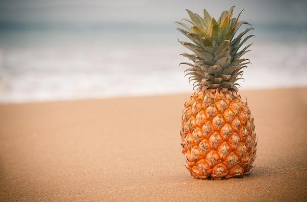 Dojrzały ananas na złotym piasku w pobliżu oceanu