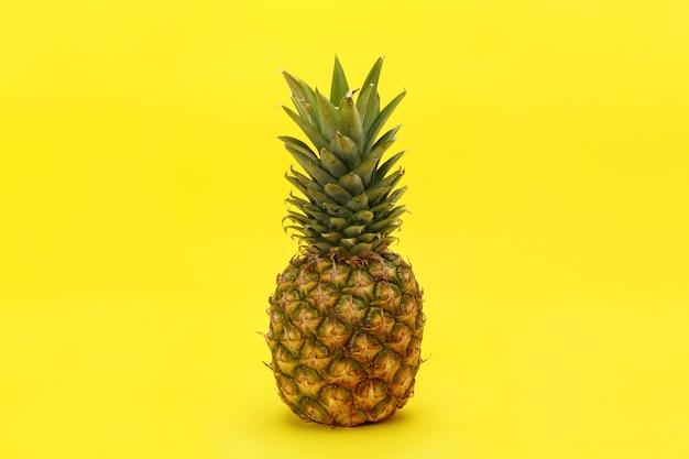 Dojrzały ananas soczysty z suchymi liśćmi na żółtym tle.