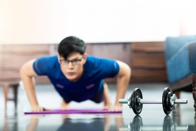 Dojrzały azjatycki mężczyzna robi ćwiczeniom w domu. trening w domu. dystans społeczny.