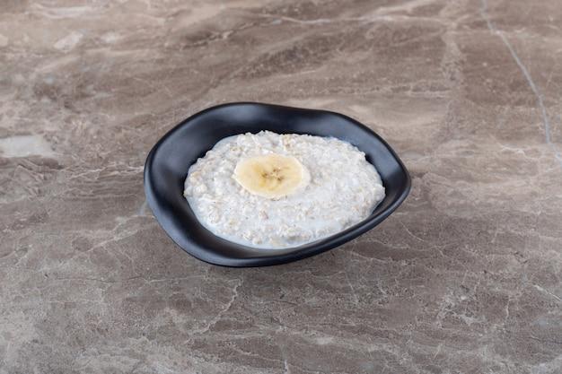 Dojrzały banan pokrojony w plasterki na misce owsianki, na marmurowej powierzchni