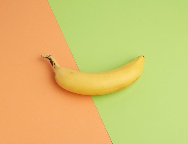 Dojrzały banan żółty na kolorowym tle, widok z góry