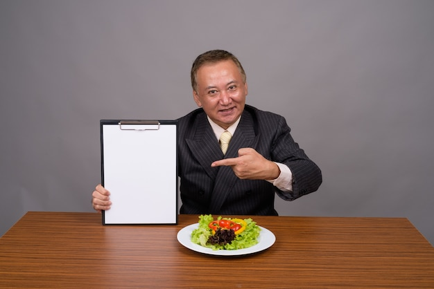 Dojrzały biznesmen azjatyckich siedzi z drewnianym stołem przed szarością
